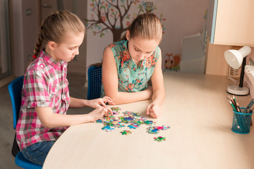Two little girls solving puzzle together
