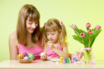Child girl with her her mom coloring Easter eggs at home