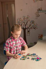 Cute little girl solving puzzle together