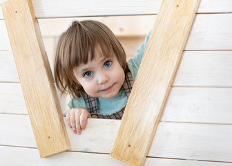 Cute child girl looks out the window of wooden toy house