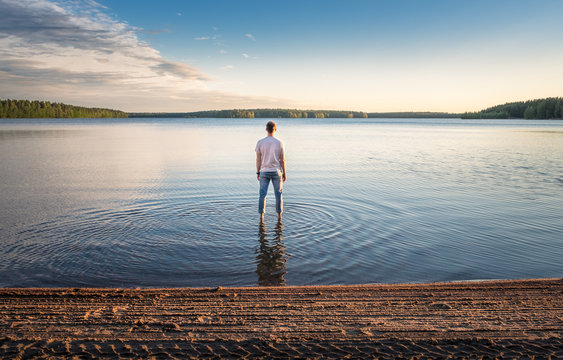 Man standing in water at beautiful summer day with idyllic lake and tranquil evening in Finland