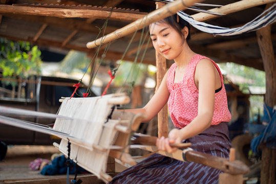 Young women weaving with traditional Thai weaving machine