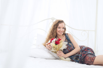 Young woman lying on bed with flower bouquet