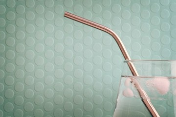 Glass of water with ice and a stainless steel reusable straw on a dotted emerald green background