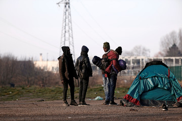 Migrants carry their belongings after the dismantling their makeshift camp near Calais Port