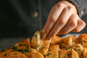 Woman eating tasty garlic bread, closeup
