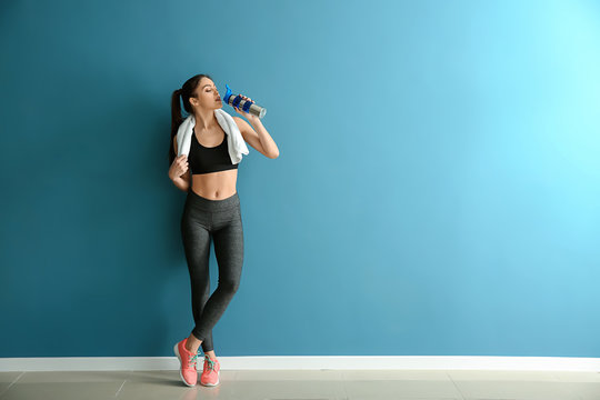 Sporty young woman with bottle of water near color wall