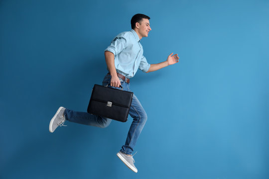 Running man with briefcase on color background