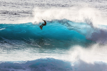 Silhouette surfer riding the big blue surf waves on the island Madeira, Portugal, a popular surfing tourist destination