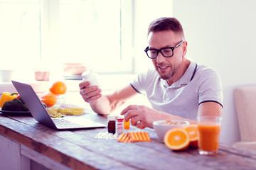 Bearded mature man feeling excited before adding supplements into his diet