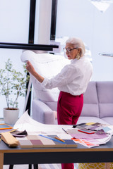 Stylish attractive elderly business dame comparing two project drawings