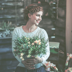 portrait of a beautiful happy young woman with a bouquet of flowers