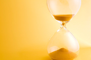 Hourglass with sand running through the bulbs on yellow background