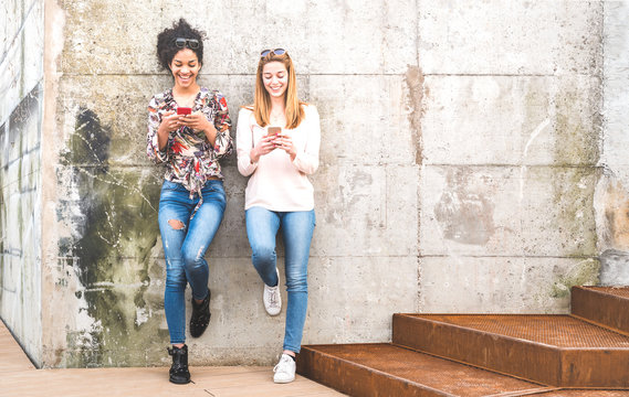 Happy girls best friends having fun outdoors with mobile smart phone - Friendship concept with millenial girlfriends on smartphones - Modern female lifestyle with women fashion blogger influencers