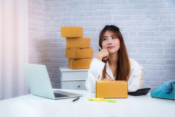 Women small business owner working at home with packing box on workplace. online shopping SME entrepreneur or freelance working concept.