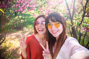 Image of young happy women friends standing in blossom spring park. Looking at camera make selfie.