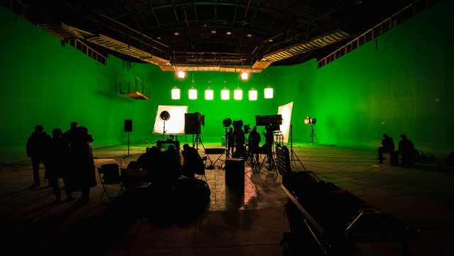 Behind the scenes or the making of film video production and movie crew team working in silhouette of camera and equipment set in studio