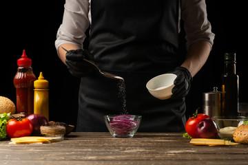 Cook marinates a red onion for a burger, a burger recipe. A recipe for cooking, making a juicy hamburger, a menu, homemade recipes. Horizontal photos