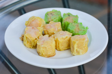 Green and yellow hot Chinese shrimp dumplings steamed in white dish for served in morning. Food and appetizer.