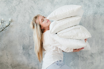 Making bed. Morning chores concept. Woman holding pile of pillows on grey background.