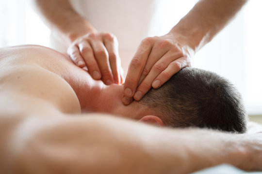 Image of hands masseur doing massage to young male.