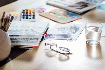 Artist workplace. Creating atmosphere. Sketchbook and palette supplies around.