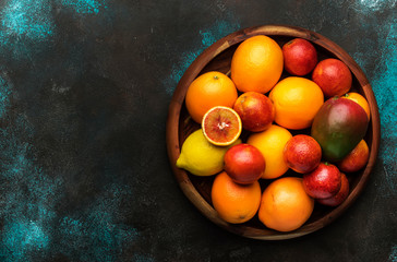 Bright fruits in large tray: oranges, lemons, mango in assortment. View from above