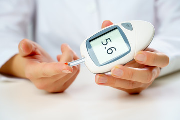 Photo of patient's hand with glucometer.