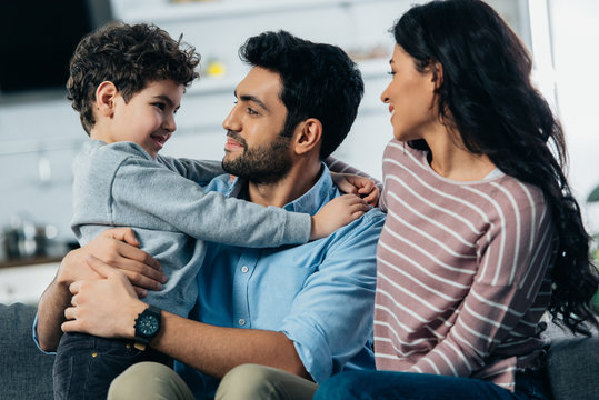 happy latin father hugging cute son near wife at home
