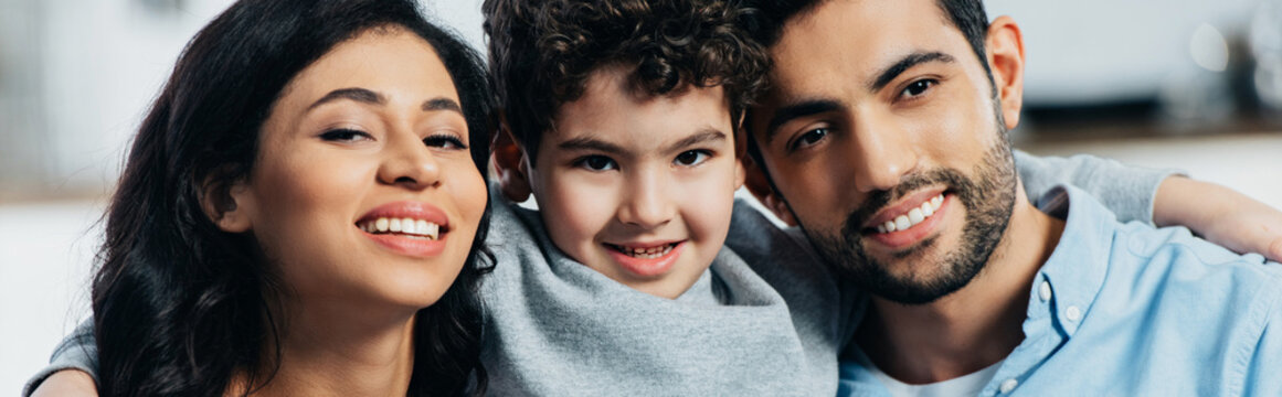 happy latin family smiling while looking at camera at home