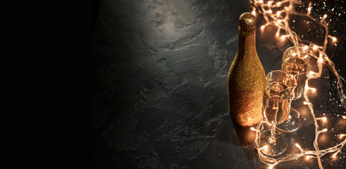 Image of golden champagne bottle, two wine glasses, burning garland on black background
