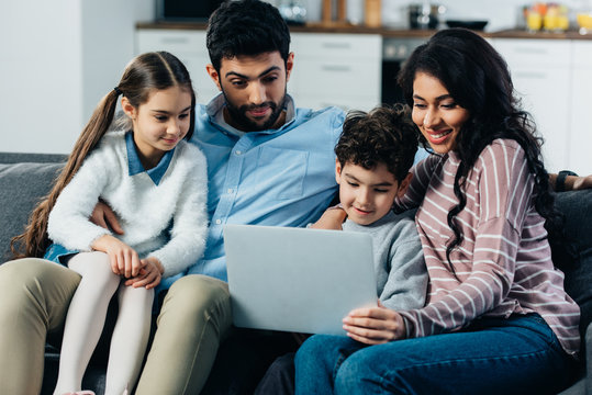 happy hispanic family looking at laptop at home