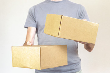 Caucasian man with gray tshirt carrying two parcel boxes on white background