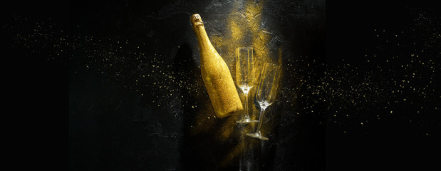 Romantic image of golden champagne bottle, two wine glasses on black stone background