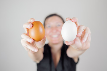 Caucasian woman with black shirt holding and showing two eggs between her fingers, blurry face on white background