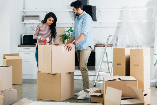 cheerful latin couple packing boxes while moving to new home