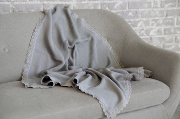 On the background of a gray brick wall there is a gray sofa on which lies a refined gray plaid with a embroidered piece.