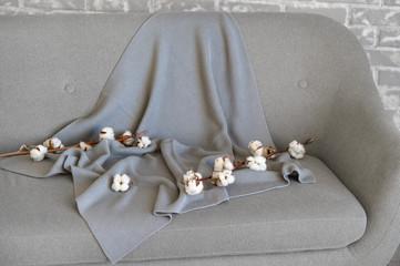 Delicate white cotton flowers textile clothes on a sofa. Organic cotton clothing idea