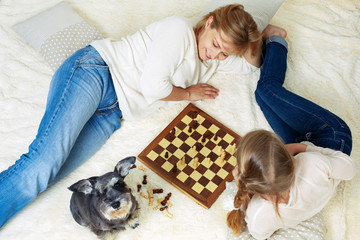 Mother and child are playing chess while spending time together at home. View from above