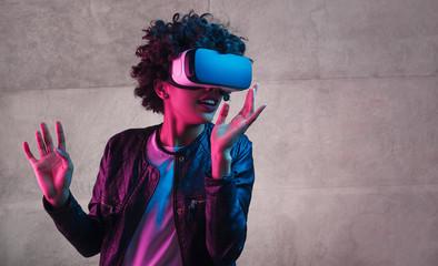 Teenager in VR glasses gesturing and looking away Wall mural