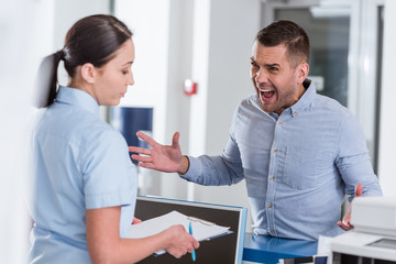 Aggressive man yelling at nurse in clinic