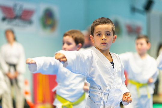Children trying new martial moves in practice during karate class in gym interior