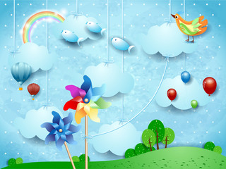 Surreal landscape with hanging pinwheels, balloons, birds and flying fishes