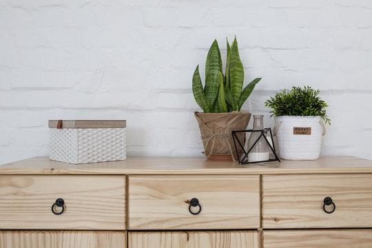 Interior living room with a wooden chest on a white brick wall