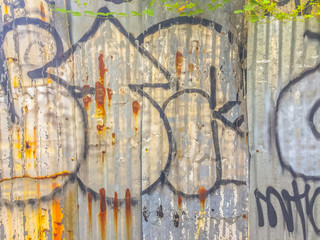 Abstract graffiti on galvanized corrugated iron metal sheet surface background. Grungy and rusty metal sheet with spray paint pattern.