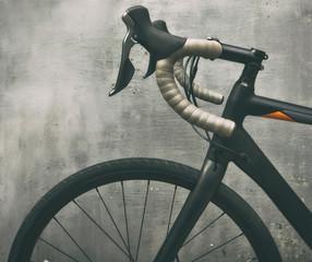 A black race bike in front of metal gray wall