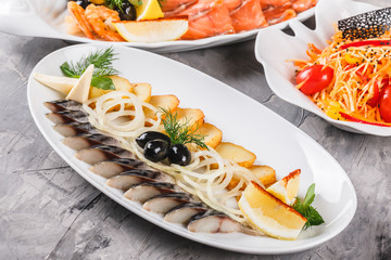 Seafood platter with smoked mackerel slice, fried potatoes, slices fish fillet, decorated with onion and lemon in plate over rustic background. Mediterranean appetizers. Top view
