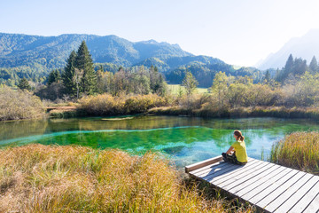 Woman sits on wooden pier by lake and beautiful landscape of nature in autumn. Beautiful woman on wooden pier by the lake outdoors. Happiness or inspiration concept. Carefree bright future concept.