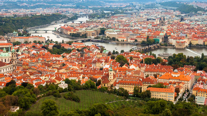 Aerial shot of Prague, Czech Republic capital, with Vltava river, many bridges and houses with orange roofs.