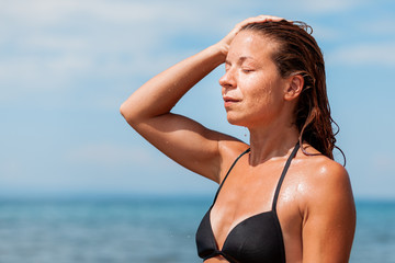 Young woman in a bikini wet from swimming in the sea